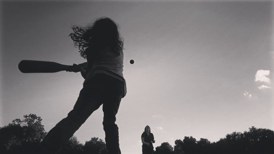 Low angle view of silhouette girl playing against sky