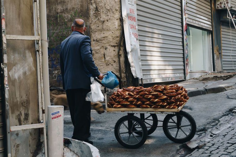 A man selling baked goods in a back alley of Istanbul. - IG: @LostBoyMemoirs (All photos taken on Sony A6300 and edited in Lightroom). Istanbul Turkey Turkish EyeEm Best Shots The Week on EyeEm Streetwise Photography Streetphotography Street Photography People People Watching people and places Travel One Person Working Lifestyles Occupation The Art Of Street Photography