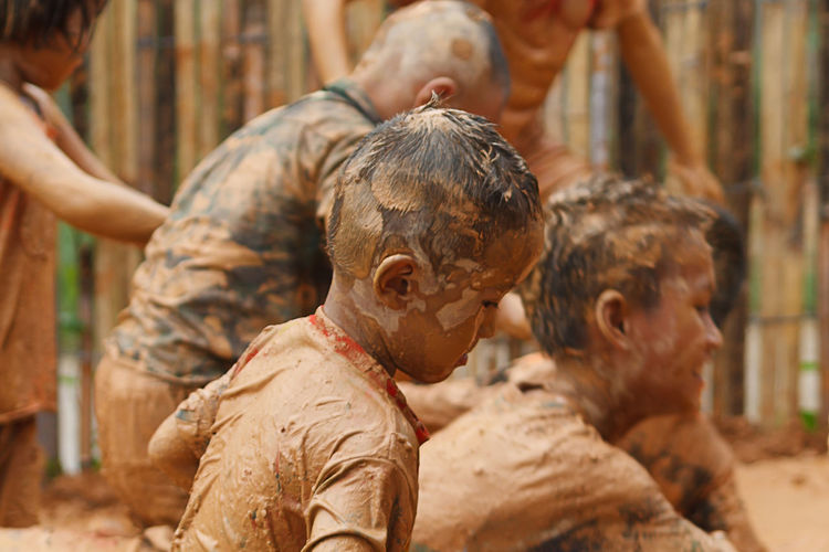 Unidentified Children's Group In Northern Village Is Playing On Clay Merrily In Chiang Mai, Thailand. Children Volunteer Close-up Day Dirt Focus On Foreground Group Of People Headshot Lifestyles Mud People Real People Wearing Friend Muddy Soil