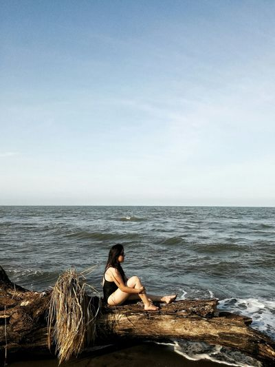 Man sitting on shore against sea against clear sky
