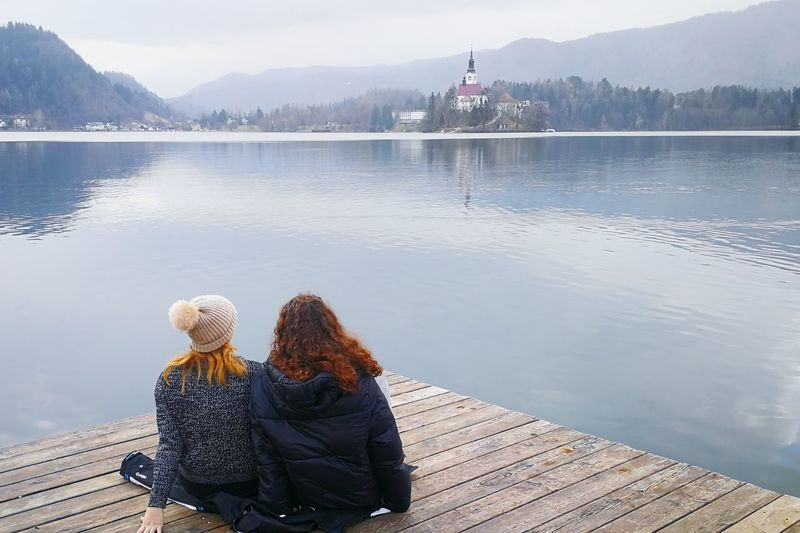 Cold outside Warm Clothing Water Young Women Women Togetherness Sitting Mountain Winter Relaxation Lake Pier Hiker Snowcapped Mountain Calm Looking At View Shore Coast Mountain Range