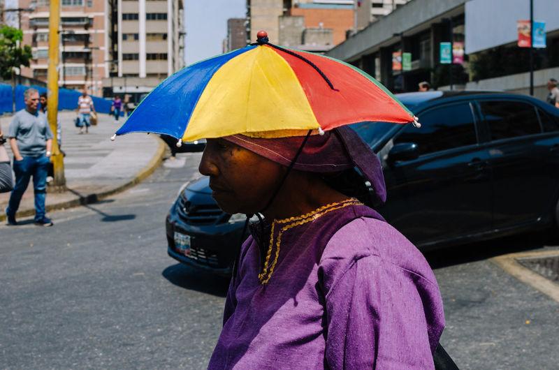 Woman with umbrella on street in rain