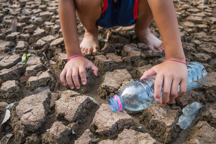 Low section of child standing bottle on barren field