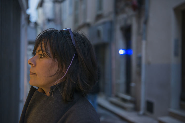 Profile view of thoughtful woman standing in city during sunset
