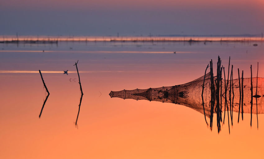 Fish net in lake against sky during sunset