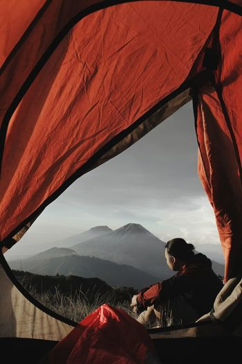 Side view of man sitting by tent against mountain and sky