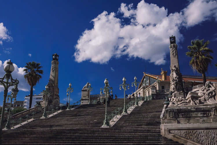 Low angle view of staircase leading towards temple against blue sky