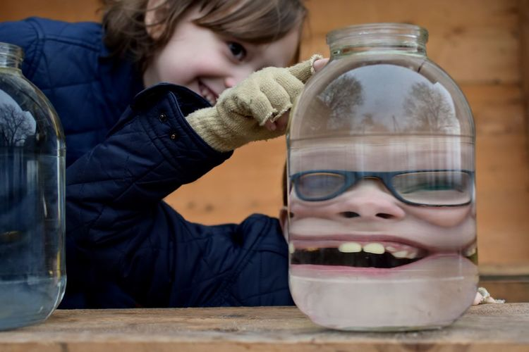 Smiling Boy In Front Of Jar On Table By Sister