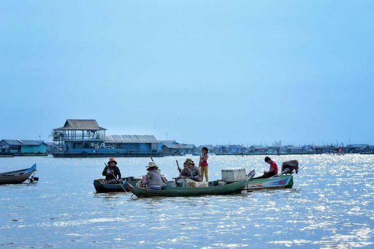 People boating in tonle sap lake against sky