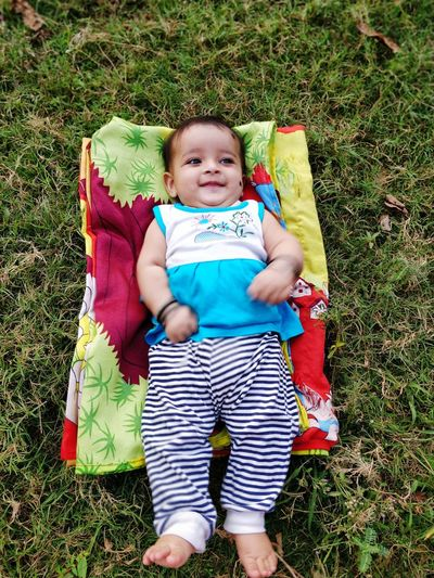 Smiling Baby Girl Lying On Sheet Over Field At Park