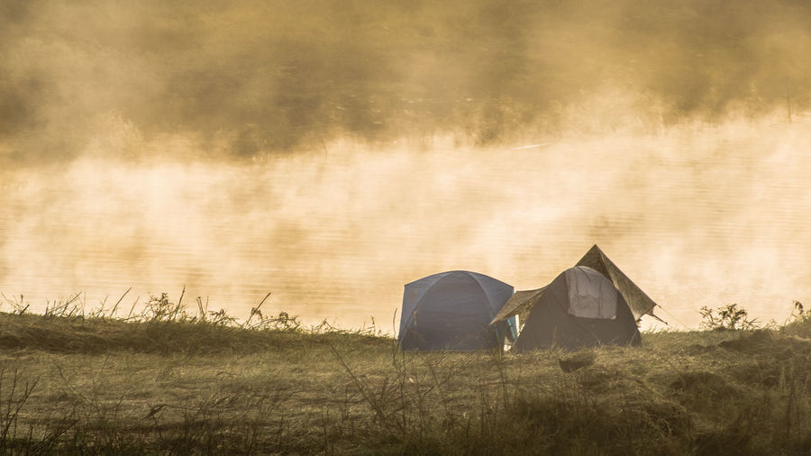 Tents on field during foggy weather