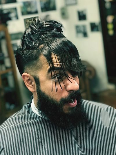 Man making face while wearing clip in hair at salon