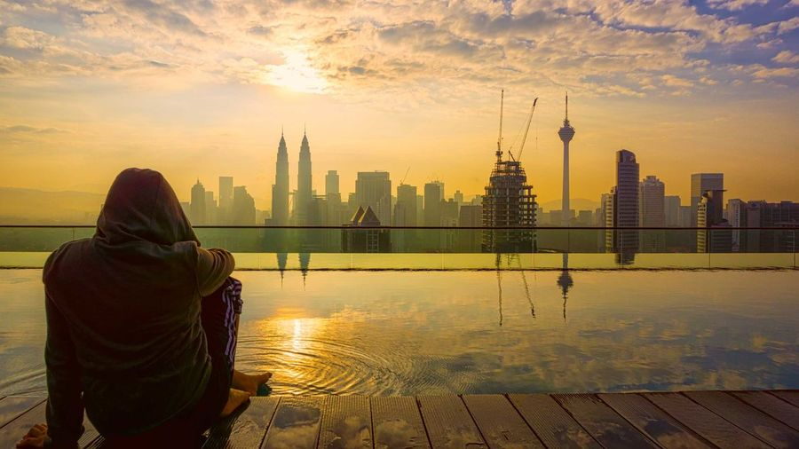 Rear view of person sitting by infinity pool with cityscape in background against sky