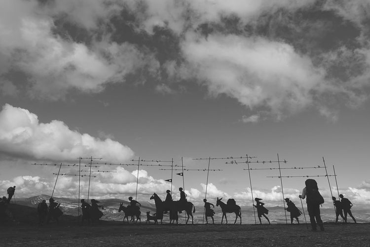 Silhouette People Walking On Field Against Sky