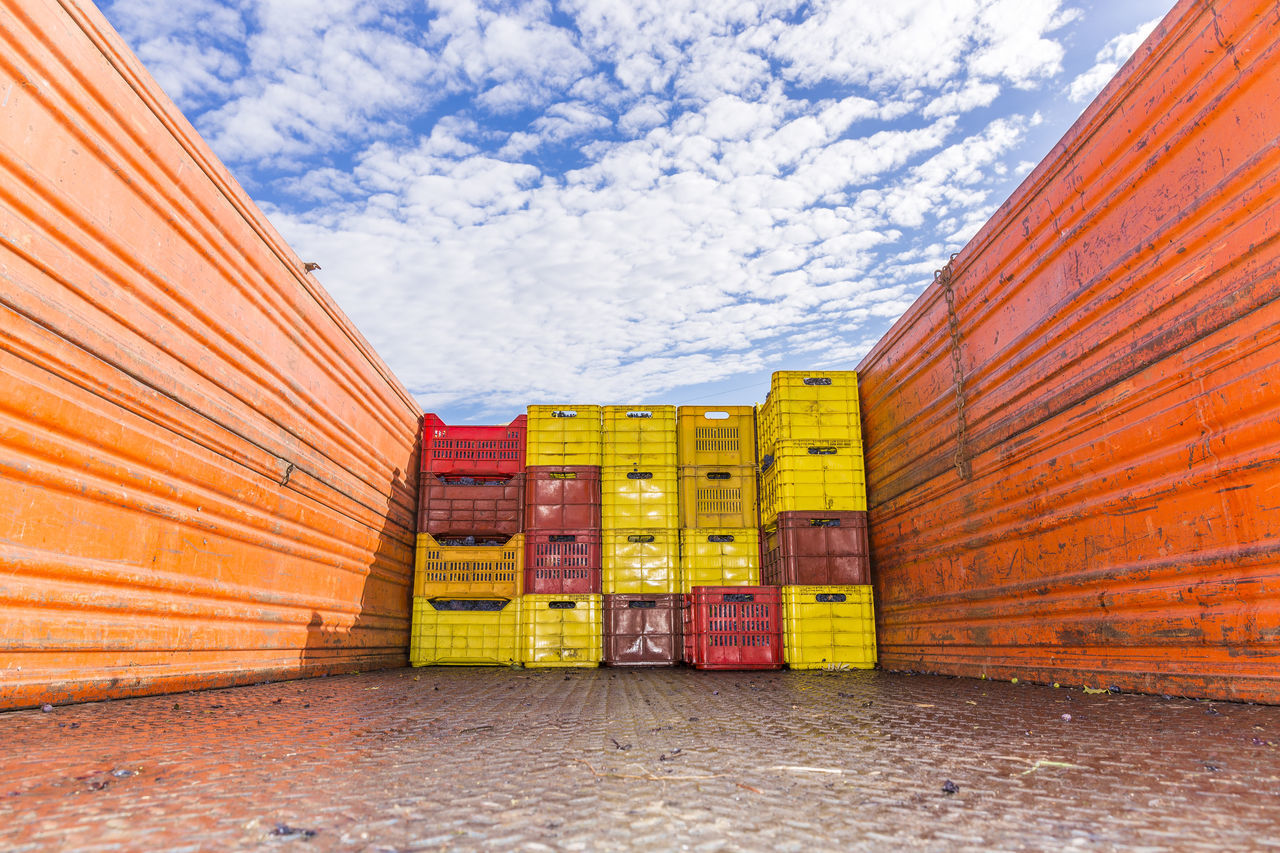 Stack Of Crates In Truck Against Cloudy Sky