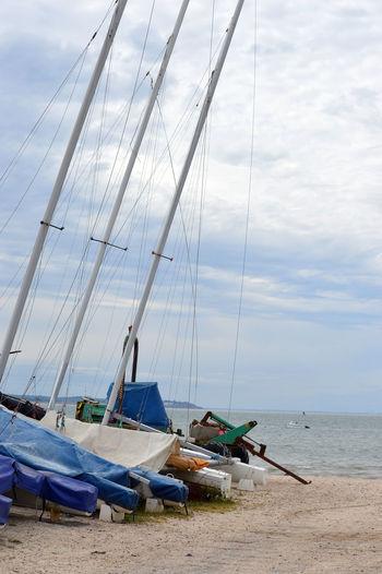 Sailboats moored on beach against sky