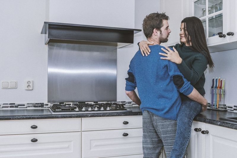 Young Couple Embracing In Kitchen At Home