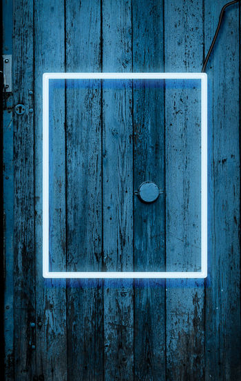 Neon glowing frame on the background of a wooden blue cracked wall, night