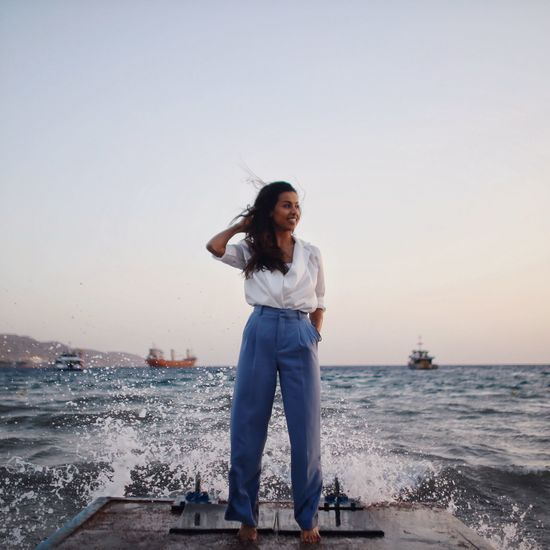 Full Length Of Young Woman Standing By Sea Against Clear Sky During Sunset