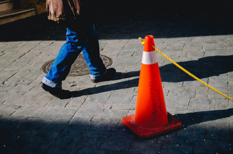 Seguridad Interna. Traffic Cone Cone Real People Low Section Day Body Part Footpath Shadow Human Body Part Human Leg Road City Safety One Person Orange Color Street Outdoors Standing Sunlight Street Photography EyeEm Best Shots EyeEm Selects The Art Of Street Photography The Street Photographer - 2019 EyeEm Awards