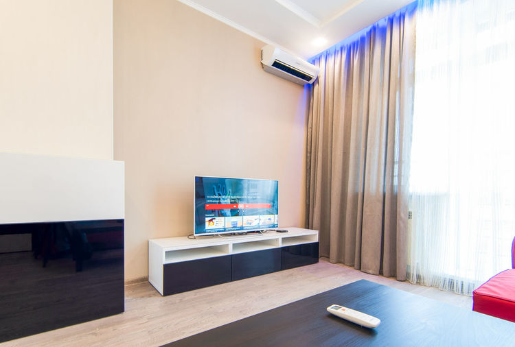 Indoors  Table Furniture Television Set Domestic Room Home Interior Technology No People Home Showcase Interior Modern Absence Flooring Seat Living Room Arts Culture And Entertainment Chair Wall - Building Feature Empty Home Flat Screen Luxury
