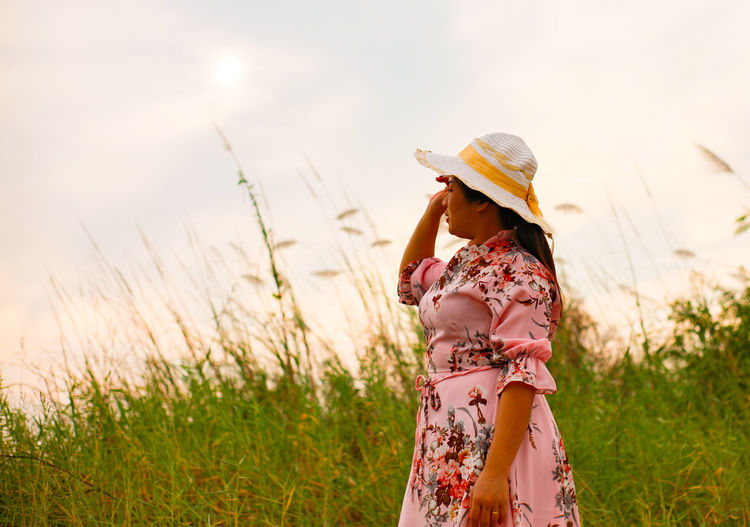 Woman wearing hat standing on field against sky during sunset