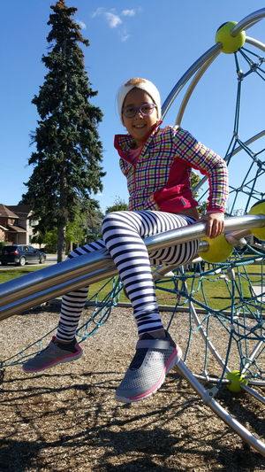 Low angle view of girl on swing in park