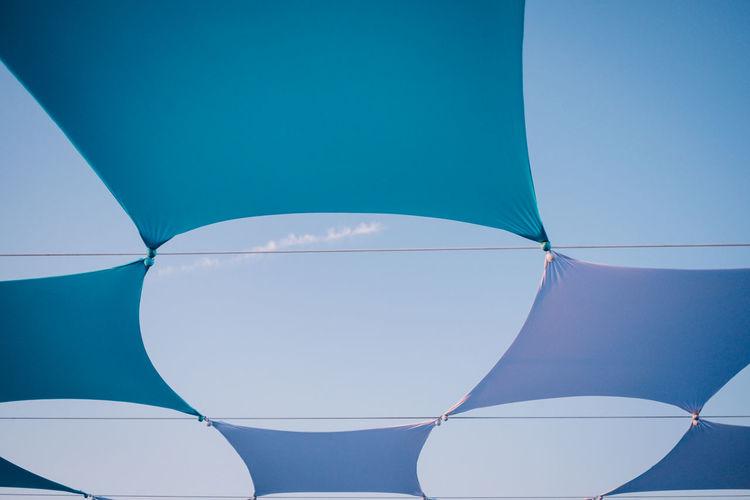Full frame shot of multi colored umbrella against blue sky