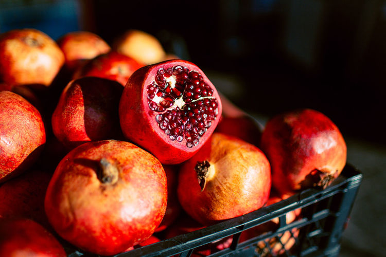 High angle close-up of pomegranates in crate for sale at market