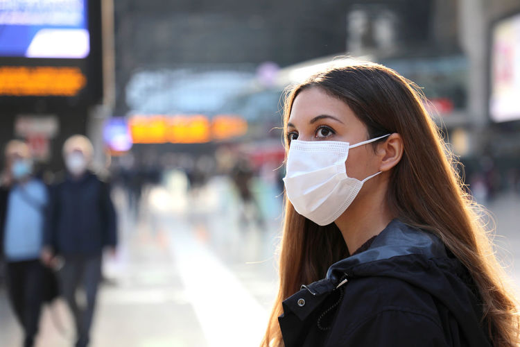 Close-up of beautiful woman wearing mask on street in city