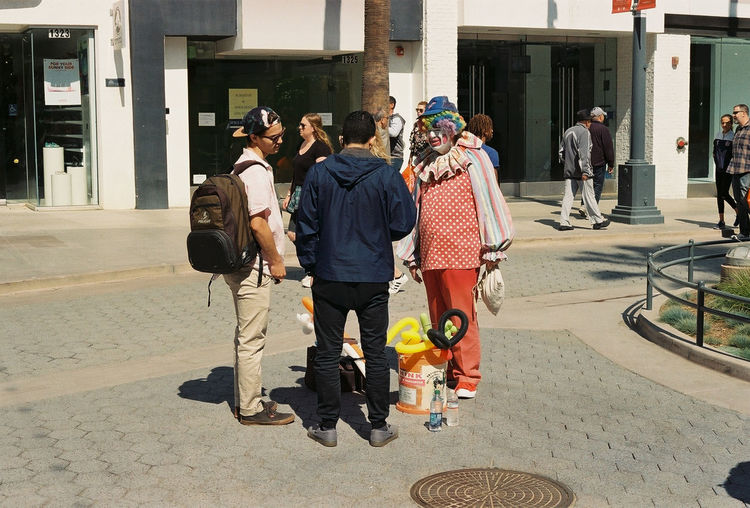 Stop clowning around. Street performer dressed as a clown talks with passerbys. - Photos taken on 35mm film with Canon AE-1 Program analog camera. Streetwise Photography Streetphotography Street Analogue Photography Analog 35mm Film Film Photography Canon AE-1 Canon Canon AE-1 Program  Kodak Kodakgold200 The Week on EyeEm Best Of EyeEm My Best Photo Medium Group Of People Walking Clown City The Art Of Street Photography