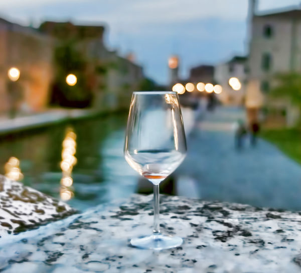 Empty wineglass on retaining wall by canal in city at dusk