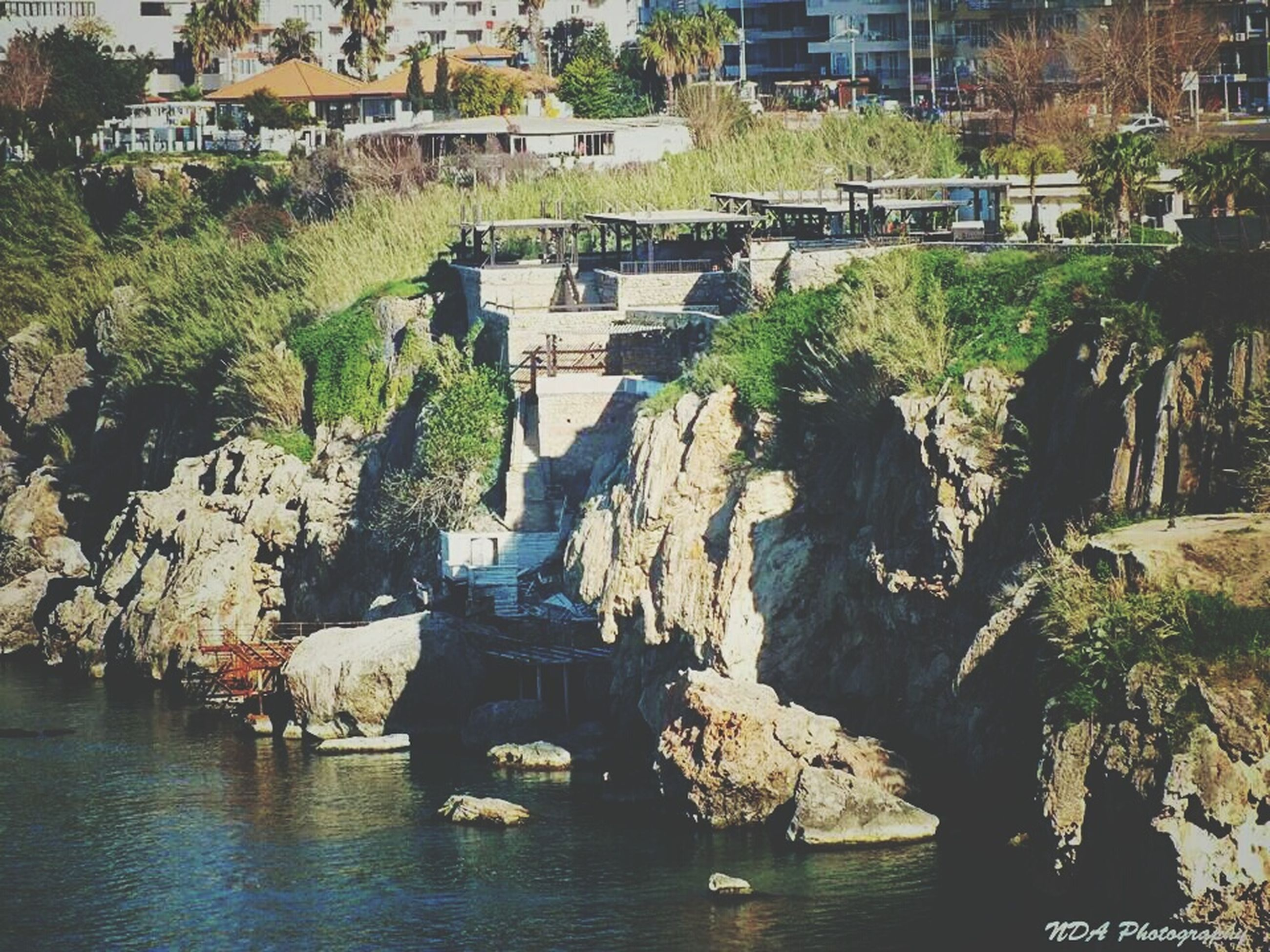 water, architecture, built structure, building exterior, waterfront, tree, river, rock - object, house, nautical vessel, day, residential building, transportation, outdoors, residential structure, nature, incidental people, boat, canal, rippled