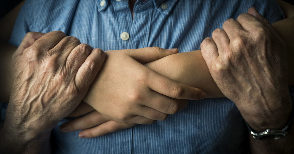 Cropped hands embracing midsection of man