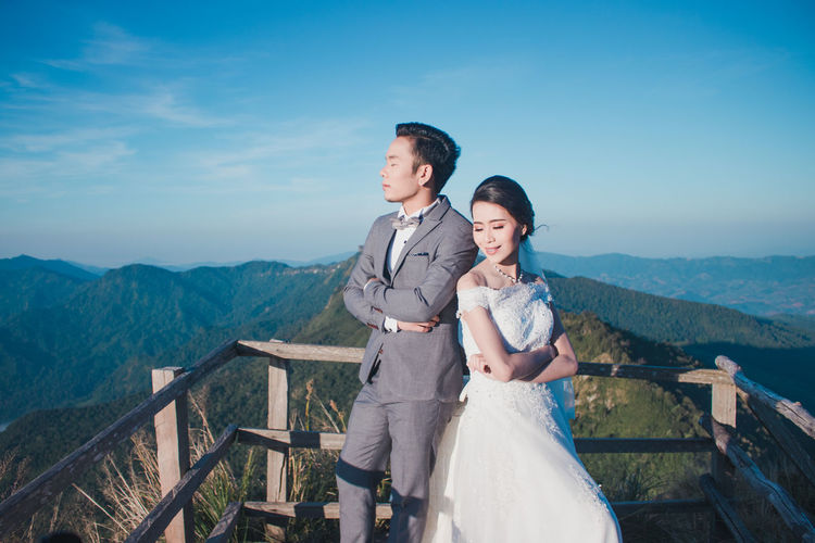 Young couple standing on mountain against sky