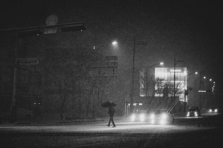 Rear view of man walking on illuminated street at night