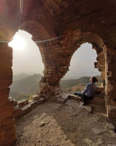 Man sitting at archway enjoy  sunset  and thinking what life go through in watchtower beijing china