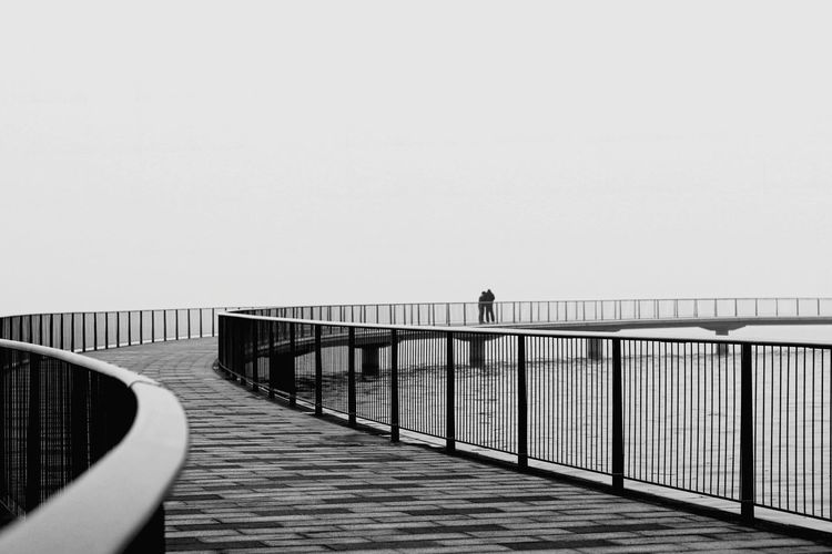 Life is a long and winding journey... Bnw_friday_eyeemchallenge Bnw_journey_2019 Blackandwhite Clear Sky Water Footbridge Bridge - Man Made Structure City Railing Copy Space Sky Horizon Over Water Wave Calm Diminishing Perspective The Way Forward Pathway