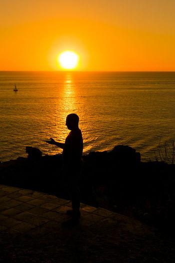 Silhouette man standing on beach against orange sky