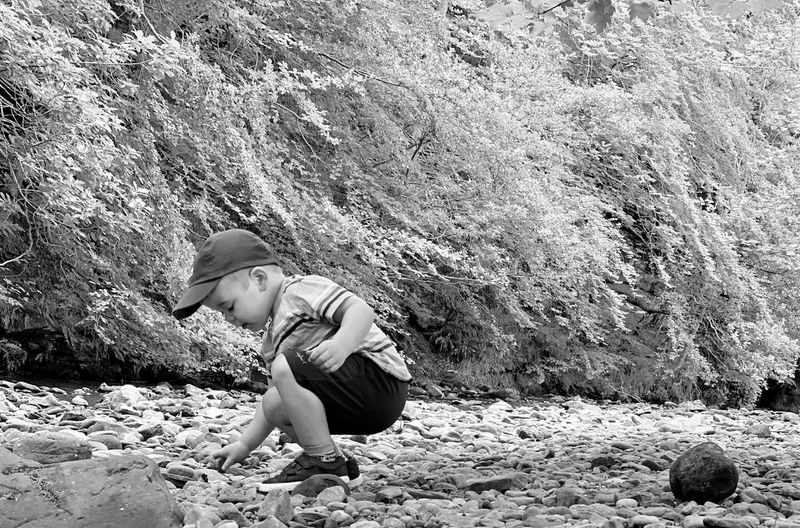 Side view of boy on rock