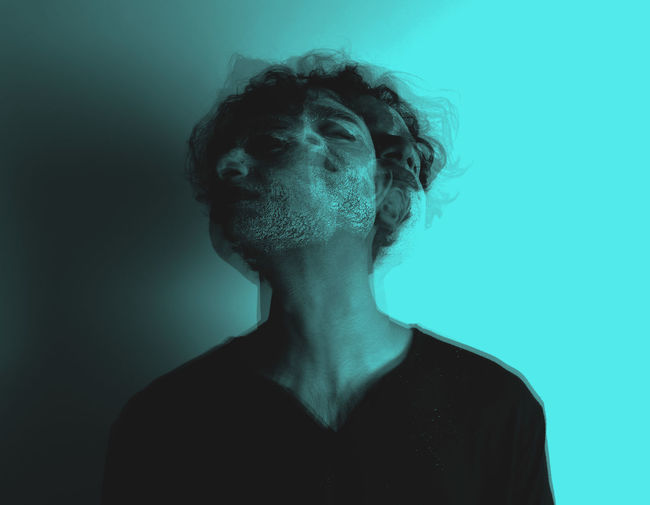 Double exposure of man with face paint against blue background