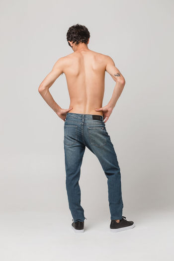 Rear view of shirtless man standing against white background