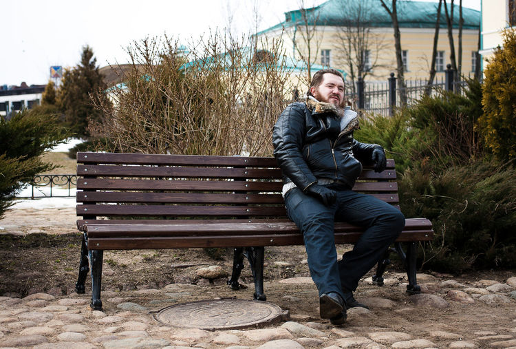 Full length of man sitting on wooden bench at park