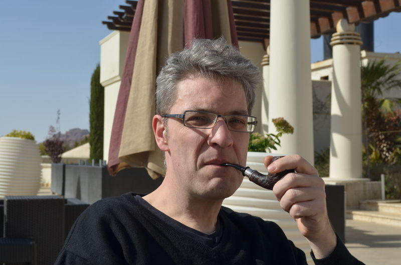 Portrait Of Mature Man Smoking Pipe Outdoors