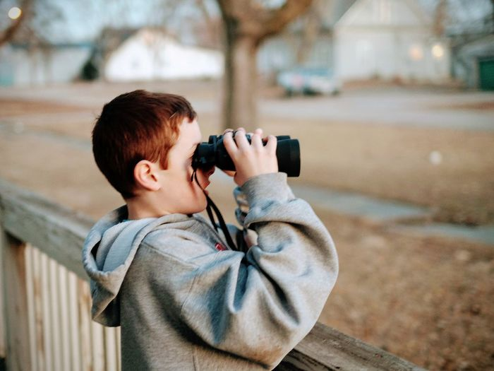 Side View Of Boy Looking Through Binoculars While Standing By Railing