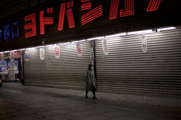 Full length of man standing on illuminated shutter