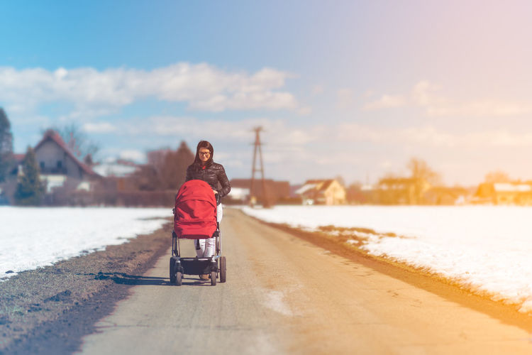 Woman with stroller walking on road against sky