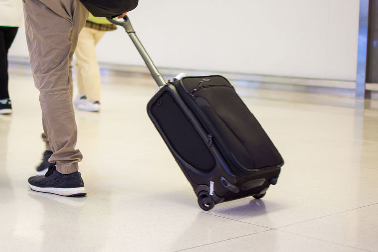 Low Section Of Man With Wheeled Luggage On Tiled Floor At Airport