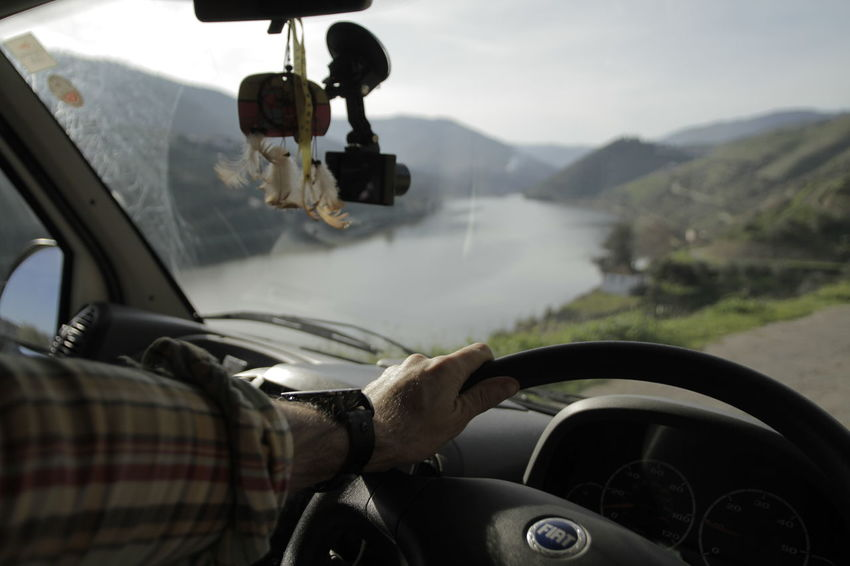 Looking through windscreen at mountain path and river Adult Car Car Interior Dashboard Day Driving Human Body Part Human Hand Journey Land Vehicle Men Mode Of Transport Mountain One Person Outdoors People Real People Road Sky Steering Wheel Transportation Vehicle Interior Water Windshield