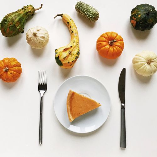 top view of a pumpkin pie in a dressing of decorative pumpkins by Thanksgiving Day Food And Drink Food Freshness Eating Utensil Still Life Table High Angle View Directly Above Fork Pumpkin Kitchen Utensil Table Knife No People Orange Color Wellbeing Plate Indoors  Healthy Eating Knife Ready-to-eat